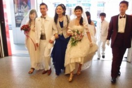 With brides and grooms in hand, Hellen happily strides into the wedding reception area.