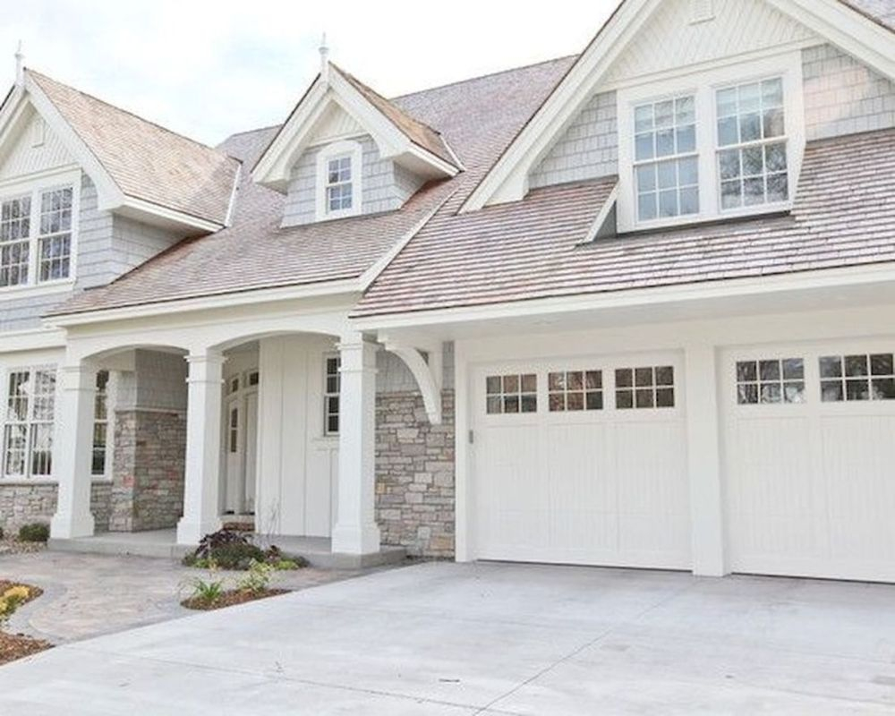 Farmhouse exterior design with white gable accents, white columns and covered porch, light colored natural stone, coordinating light colored shake roof