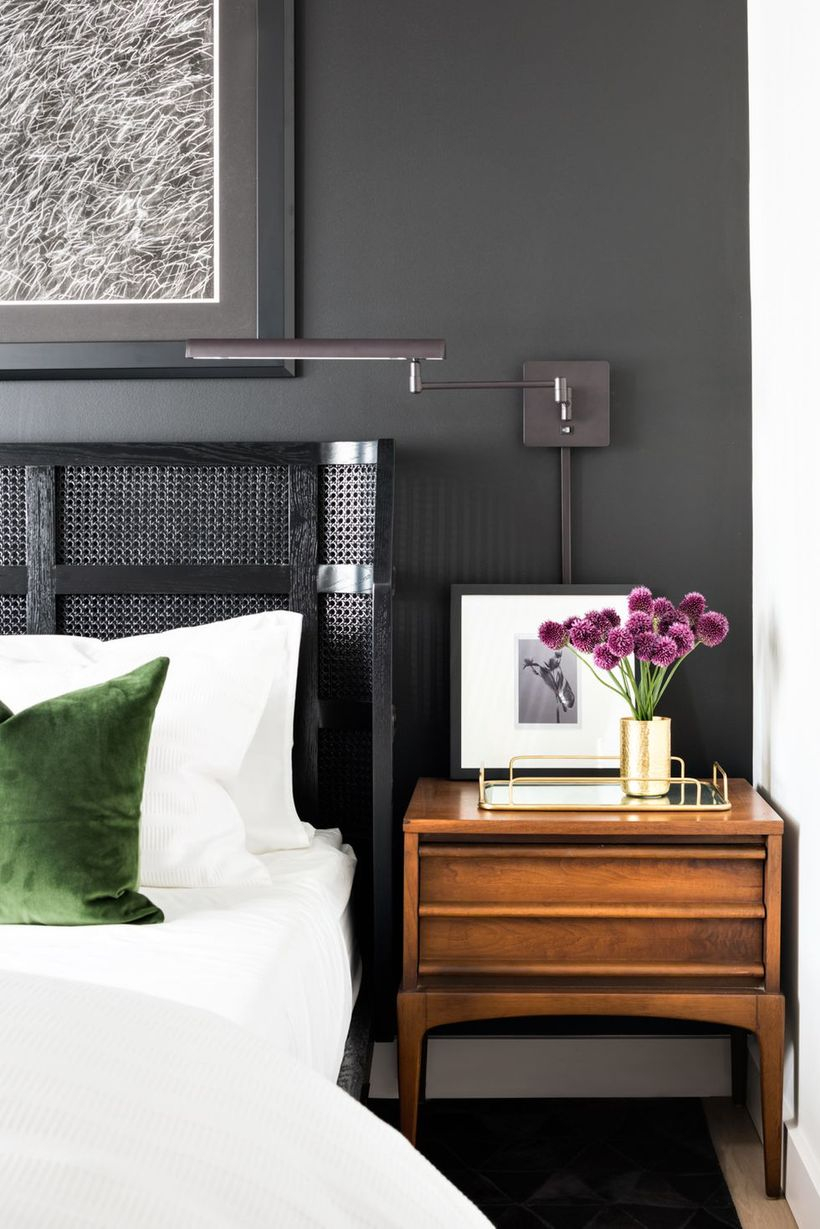 The black accent wall bedroom with a big wall art, a night stand to store a house plant and a gallery