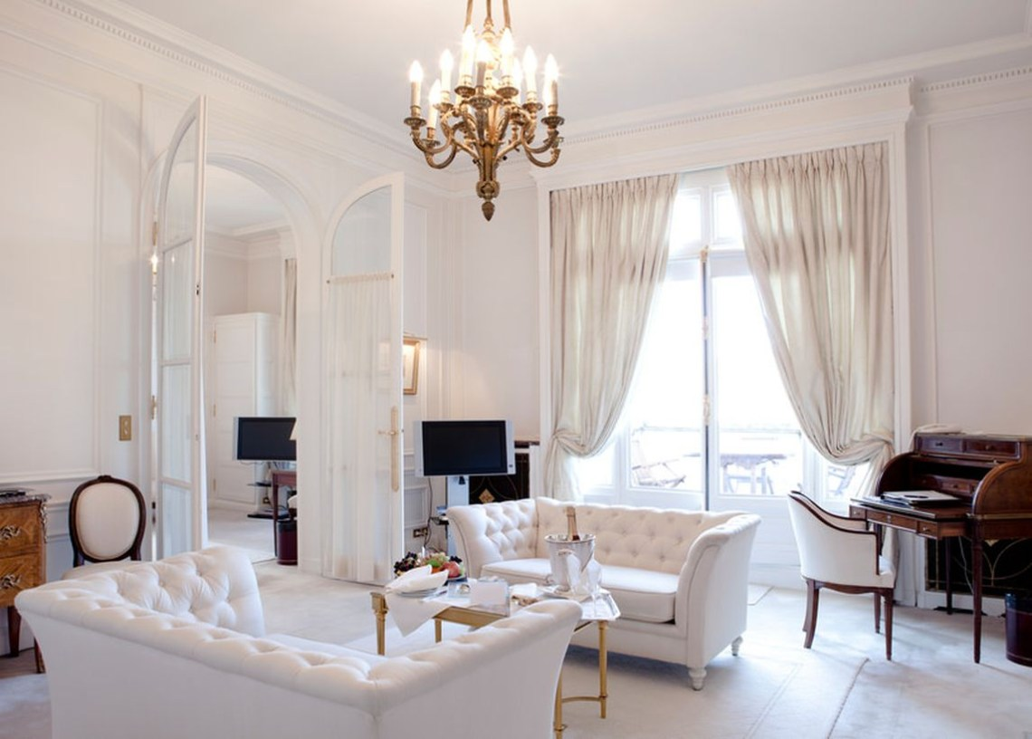 Wonderful traditional white living room from floor to ceiling. white curtains, white floor carpets, and white sofa sets to make you sleep better