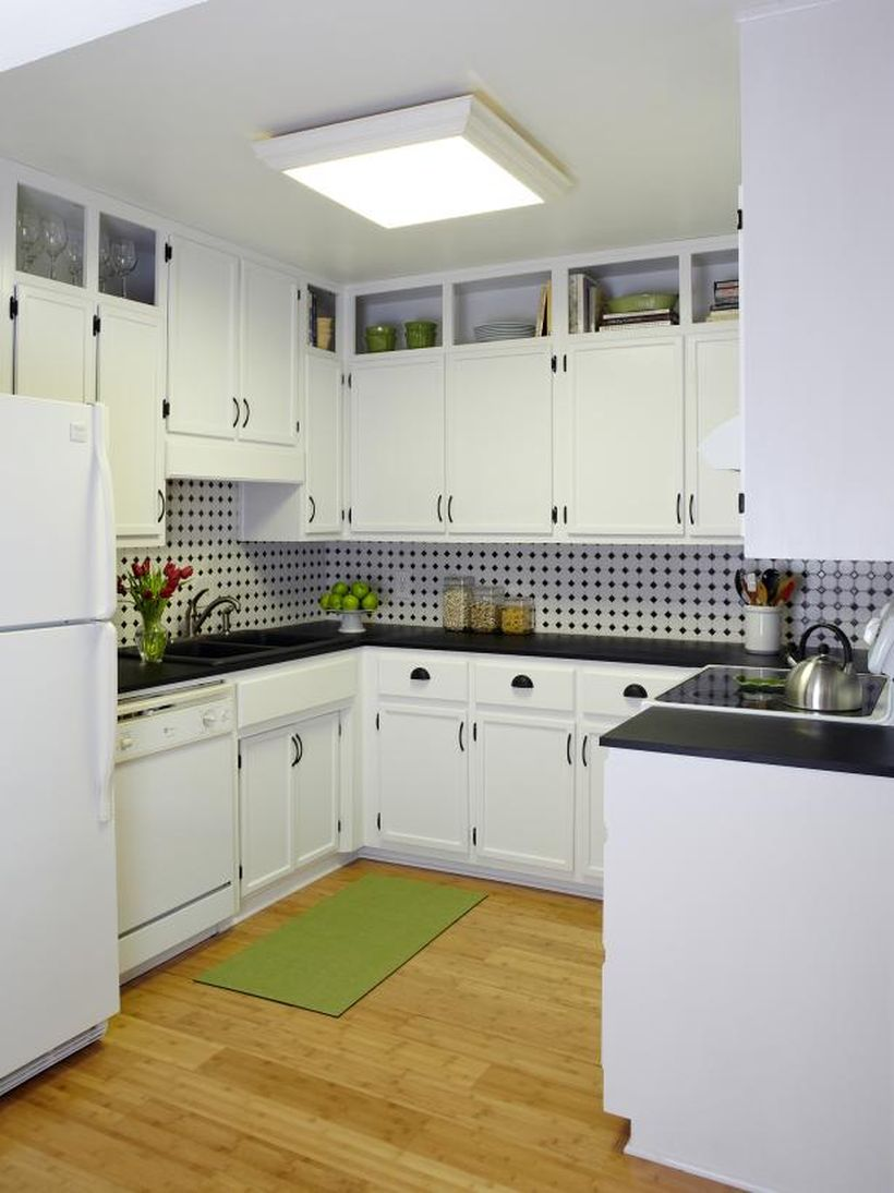 A gorgeous white kitchen design with white kitchen storage cabinets, a white refrigerator, a black granite table, and white backsplash polka dot black pattern