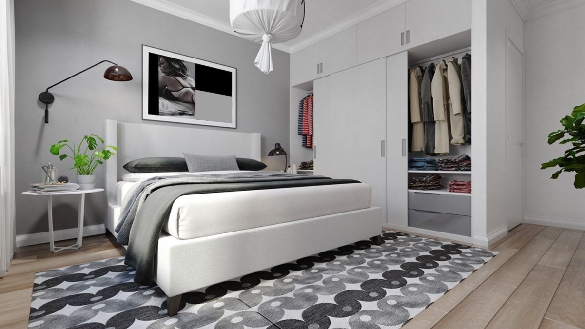 A beautiful grey bedroom with white and grey walls, a large grey wardrobe, unique pattern rug, decorative lighting, a house plant and wooden pallet floor