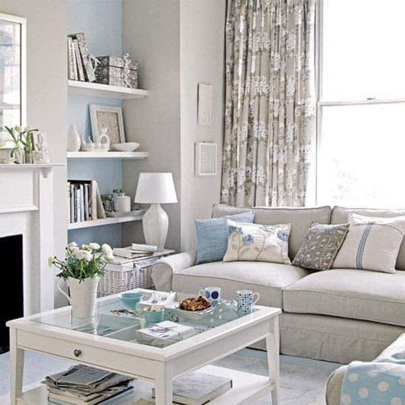A cozy living room decor ideas with pink sofas, a big window, a pattern flowers curtain on pink colour, wooden hanging racks, a coffee table, rattan basket to place table lamp