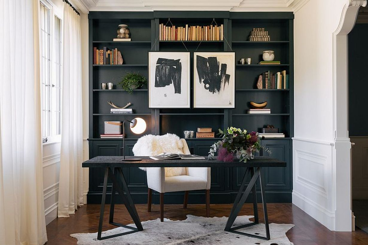 A minimalist black and white home office with white walls, a large black bookshelf, white curtains, painting hung on the bookshelf, black wooden table in the small space