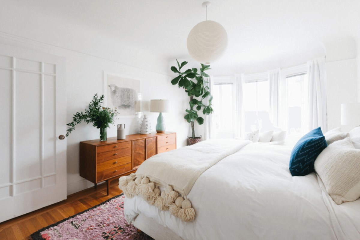 A modern bedroom design with a white sliding door, a wooden bedroom storage, white table lamps, white curtains, and house plants to create a cozy
