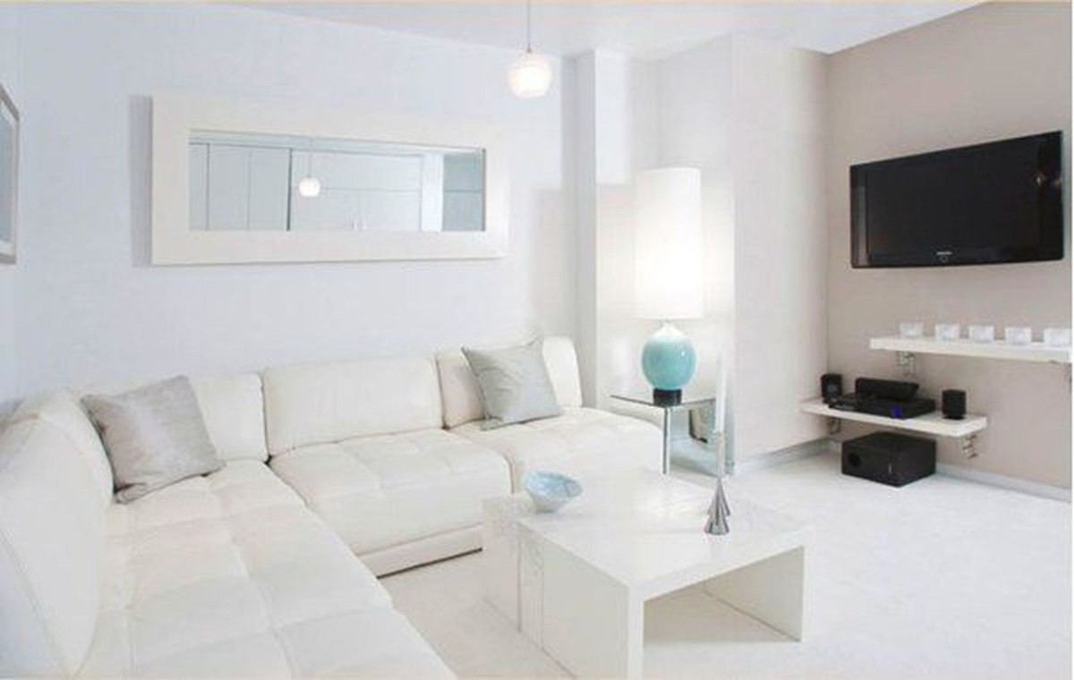 A simple white living room design with white l shaped sofas, a white coffee table, white hanging racks, a table lamp at the corner, and a tv hang on the walls