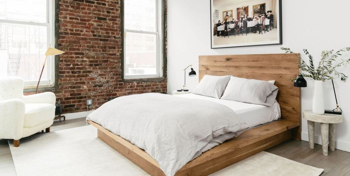 A sleek wooden bed frame and brick walls to create a cozy in the minimalis space
