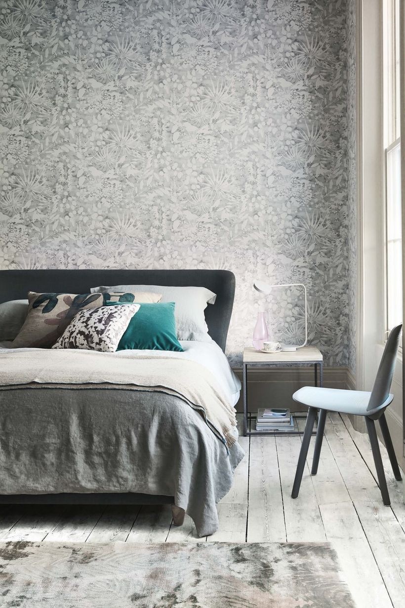 An adorable monochrome bedroom decor ideas with a grey wallpaper with unique pattern, nightstand on beside, and wooden pallet floor