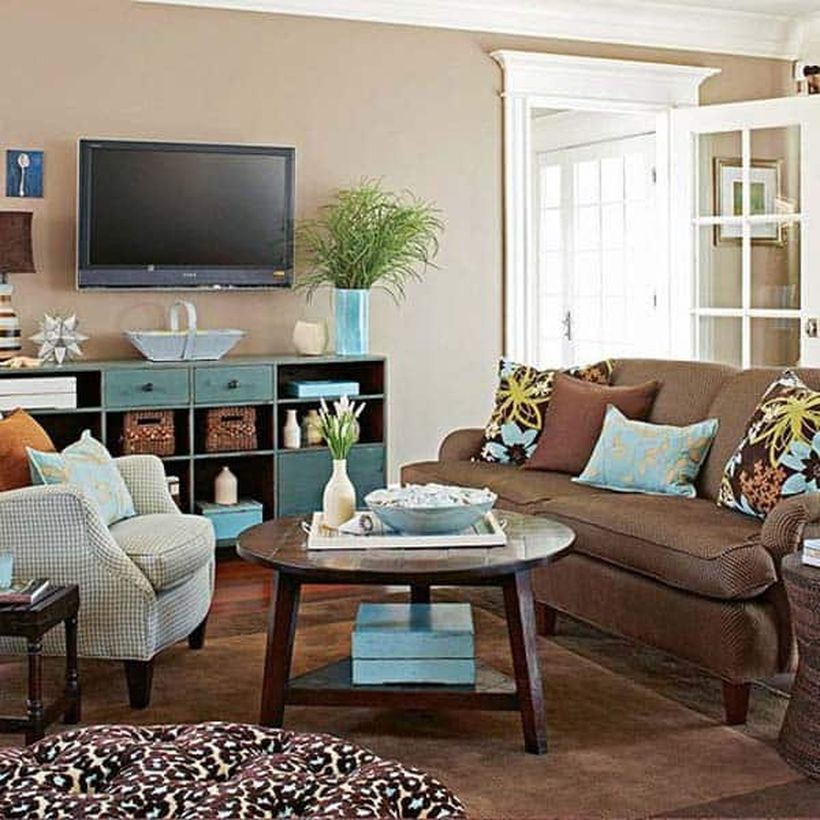 An amazing living room decor ideas with beige walls, white and brown sofas, a storage cabinet to put some accessories, a table lamp, hanging tv on the walls, a round wooden coffee table, and house plants