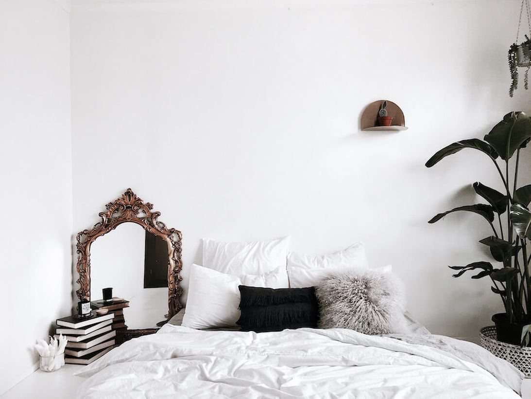 An awesome small bedroom with a hanging rack to put some house plant, a mirror at the corner, and decorative plants on the beside of bedroom to create fresh room