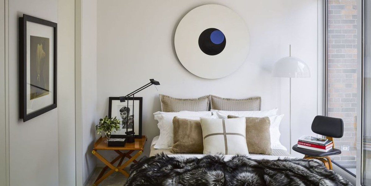 An elegant guest bedroom appeals with nightstand on beside to store gallery, rounded shapes in the lamp and artwork in the small space