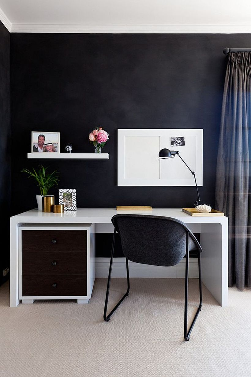 An elegant home office with a white hanging rack on the black walls, a white table, and table lamp