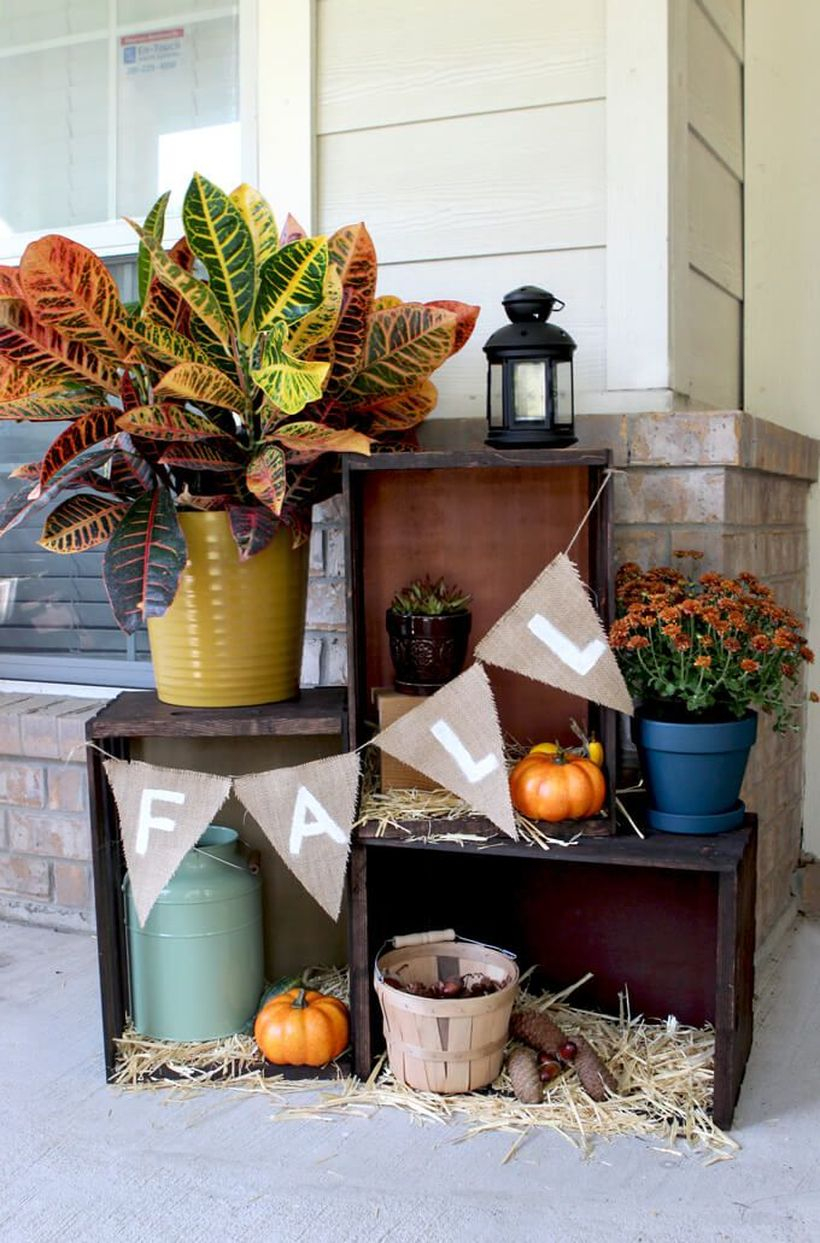A beautiful outdoor redecoration from summer to fall with pumpkin terraces, piled up several wooden crates, then line with the bottom with hay.