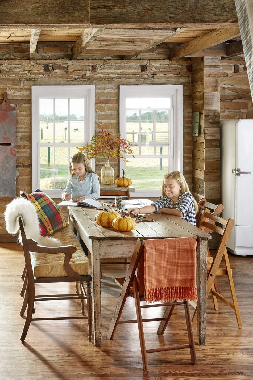 A comfortable indoor redecoration from summer to fall with blankets, pillows, and a cushioned bench will make everyone want to gather round the dinner table long after the food is gone.