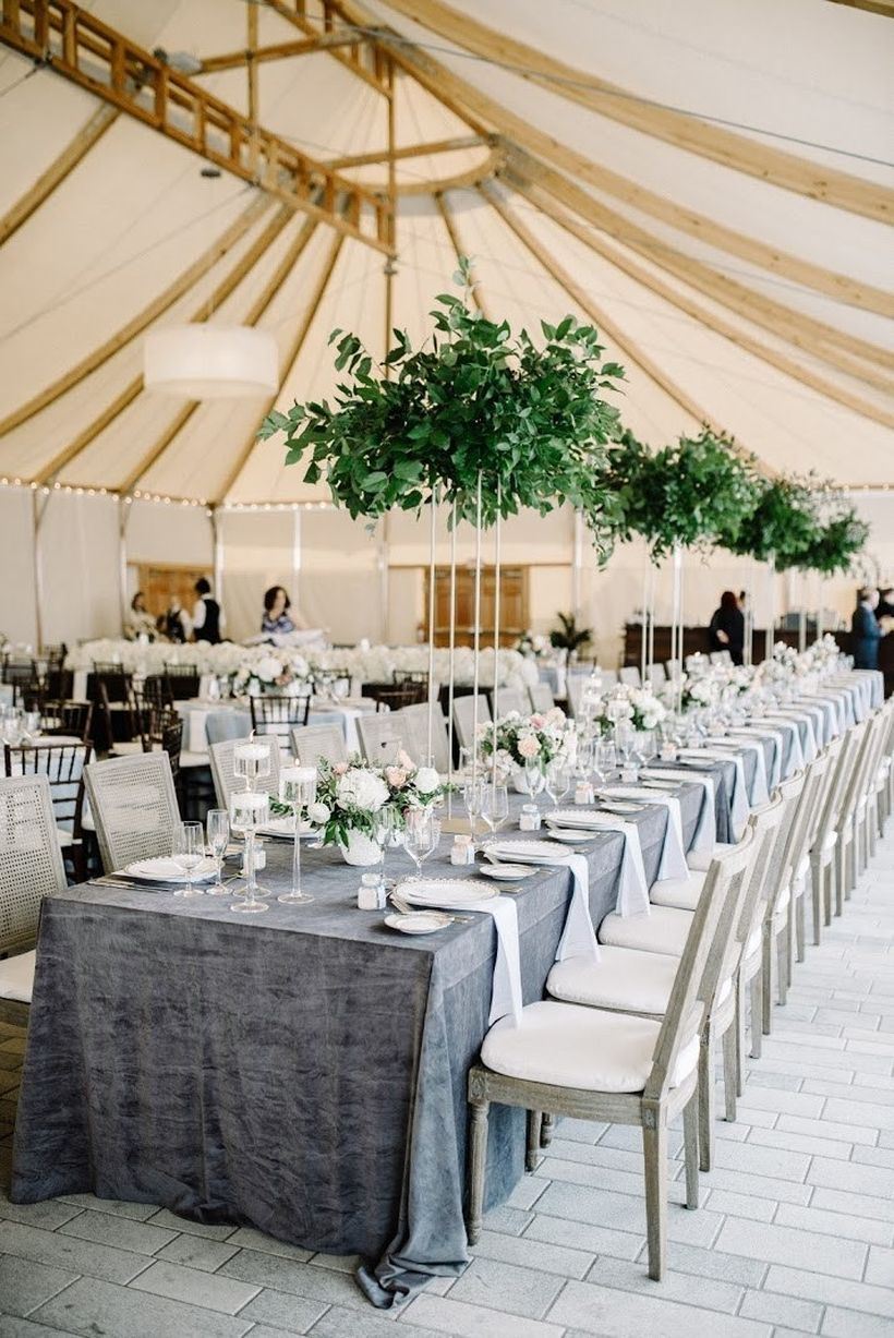 A creative indoor table set for wedding with long wooden table classic, gray tablecloth, greenery, chandeliers are a fairly inexpensive way to make an impact at your reception.