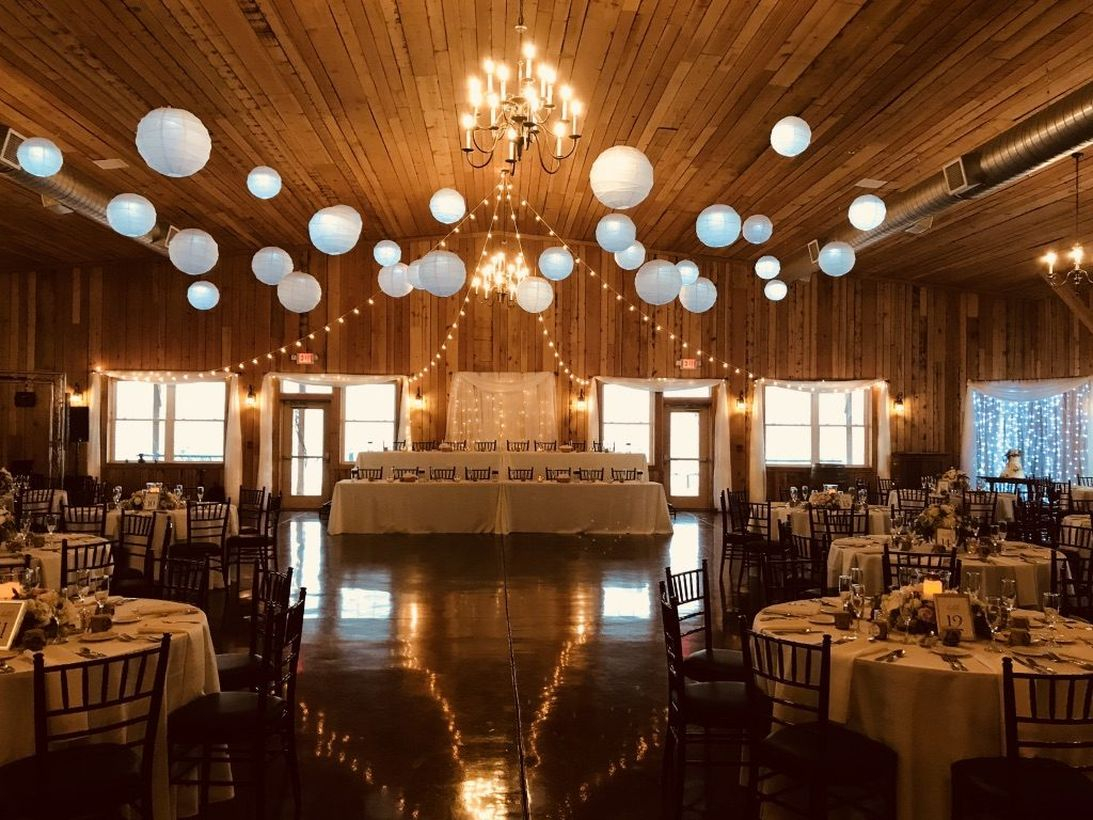A fabulous indoor venue for fall wedding with 100-year-old reclaimed barn wood and sparkling chandeliers give.