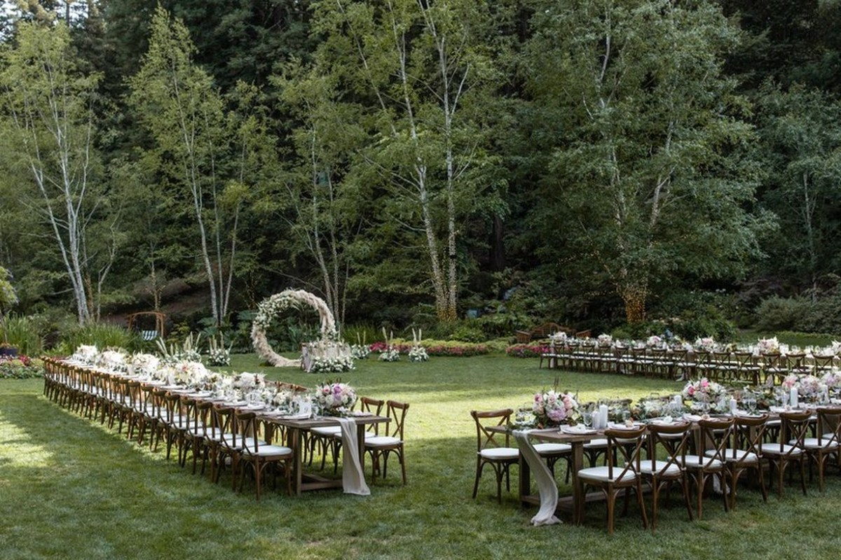 A fabulous outdoor table set for wedding with long wooden tables which is positioned u-shaped, wooden chairs classic, decoration on the table,green grass and background the forest.