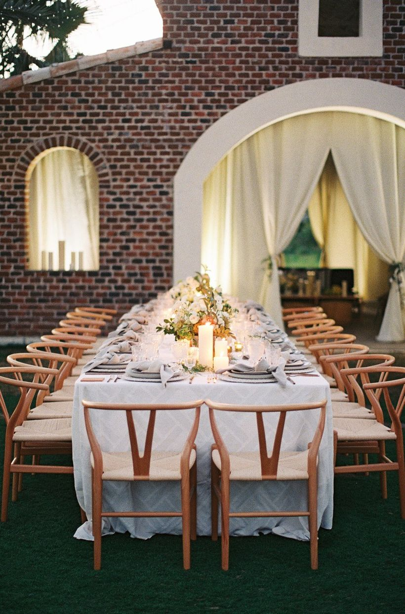 A gorgeous outdoor table set for wedding with long table, white tablecloth, wooden chairs and decoration on the table green grass.