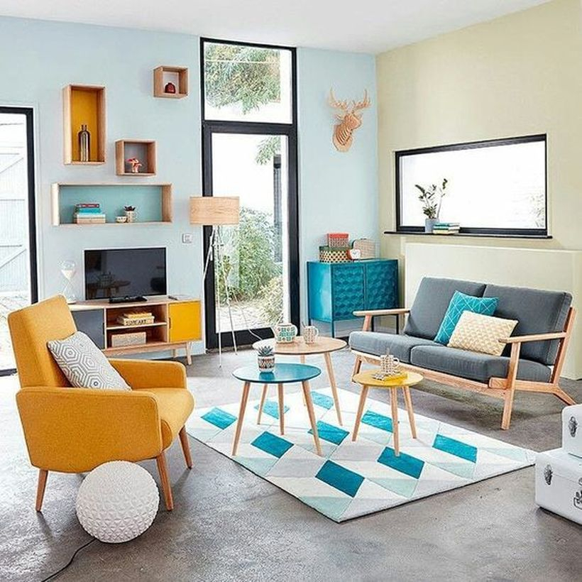 A stunning home paint colors with with blue tosca, the combination of yellow chair, geometric rug, grey sofa, colorful nesting tables, and blue cabinet