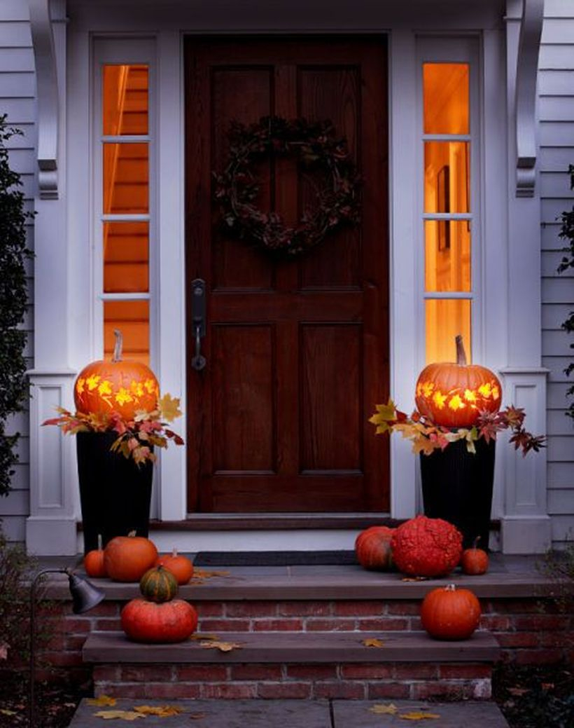 An amazing fall porch ideas with wreath, pumpkin planters and pumpkin light on the black pot