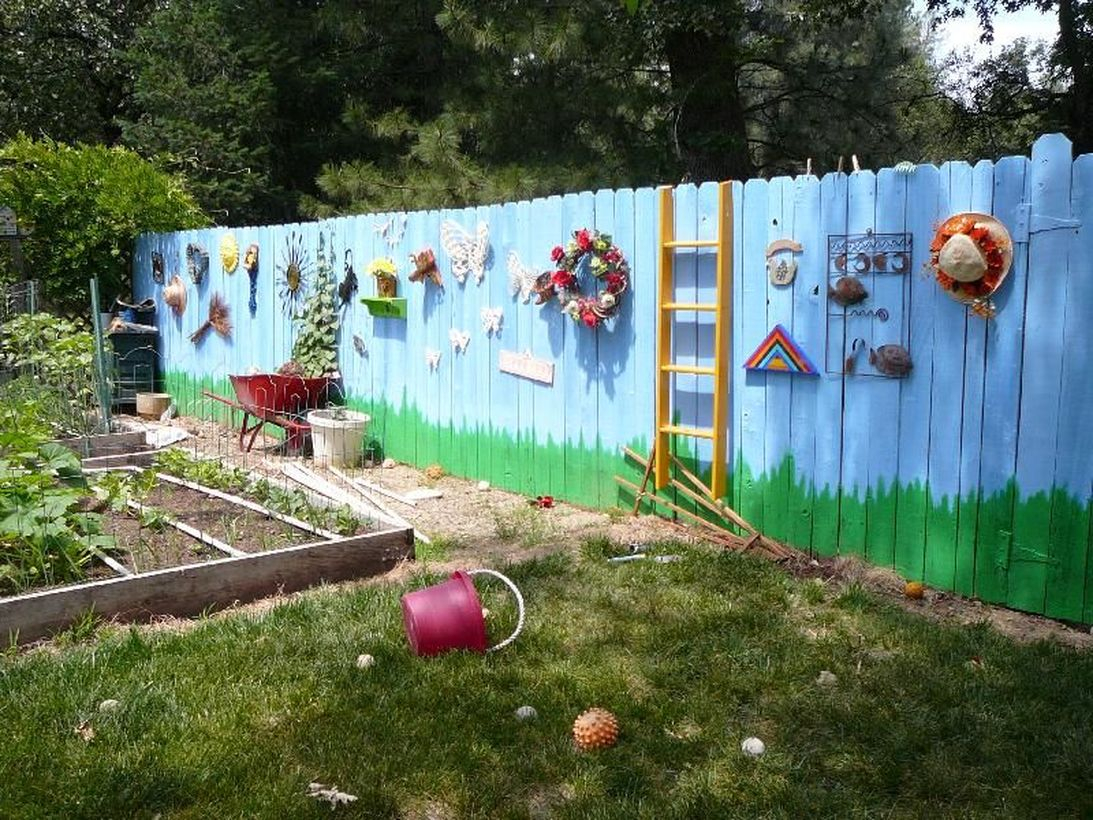 An adorable painting fence for garden with sky painted fence, grass and attach all kinds of knick-knacks hanging pleasant household appliances on the fence against a landscape background.