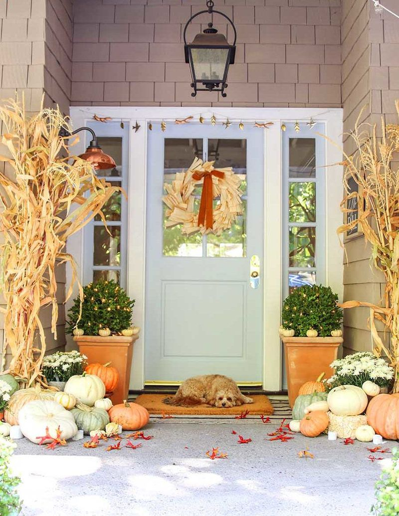 An amazing fall outdoor decoration with matching corn stalks, an array of pastel pumpkins, and a charming door wreath bring this neutral color palette to life