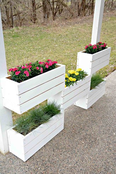 An awesome diy tiered wood flower boxes with red and yellow flowers to beautify your garden