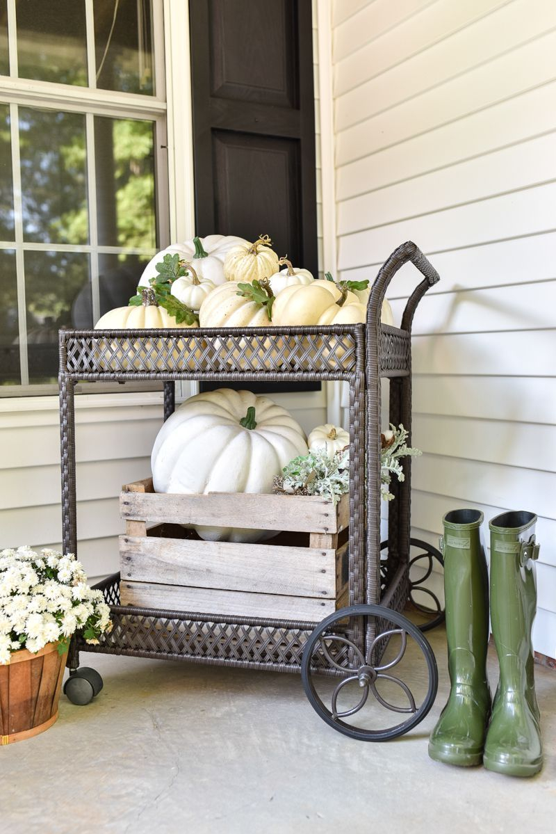 An awesome outdoor bar cart to decorate this fall combine with flowers decoration, boots and pumpkins on each shelf