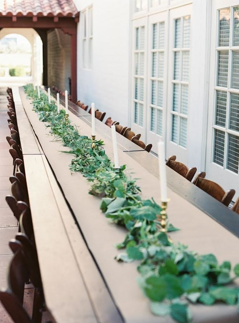 An elegant outdoor table set for wedding with wooden tables, craft paper, a garland made only of greenery and candlesticks to round out this classic look.