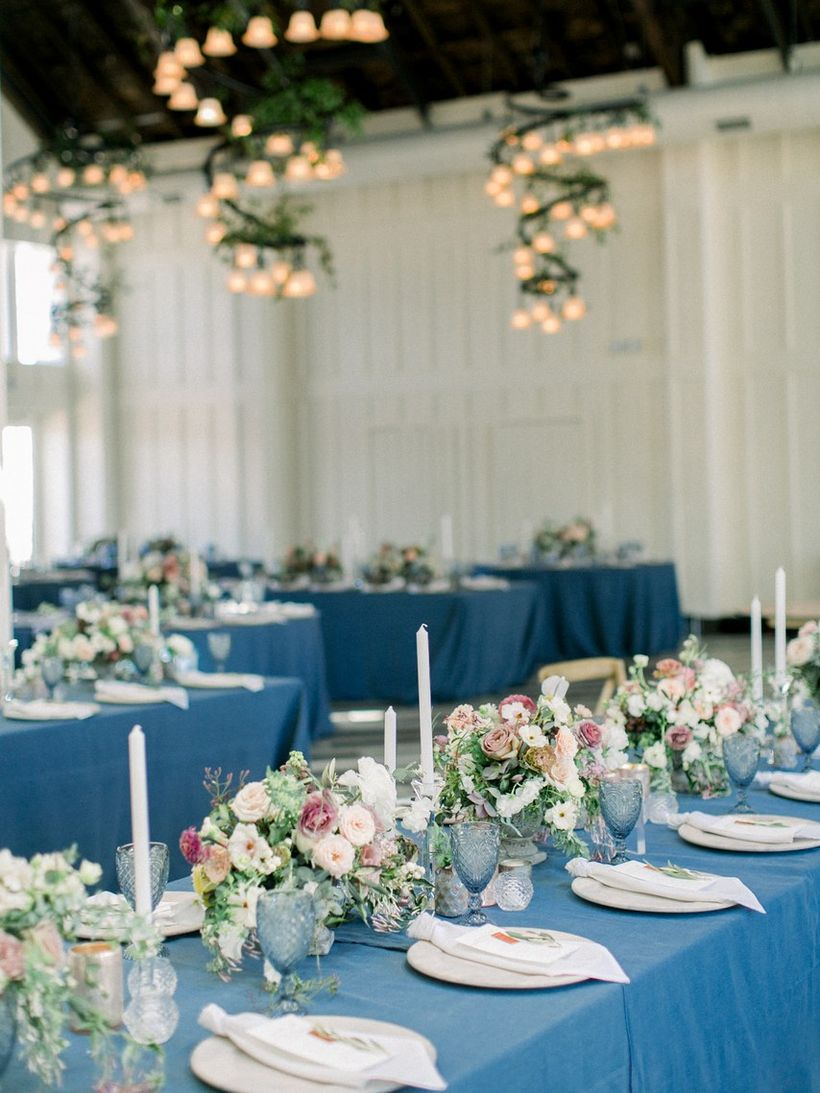 An impressive indoor table set for wedding with long tables feel dramatic and interesting with colored linens in surprising palettes instead.