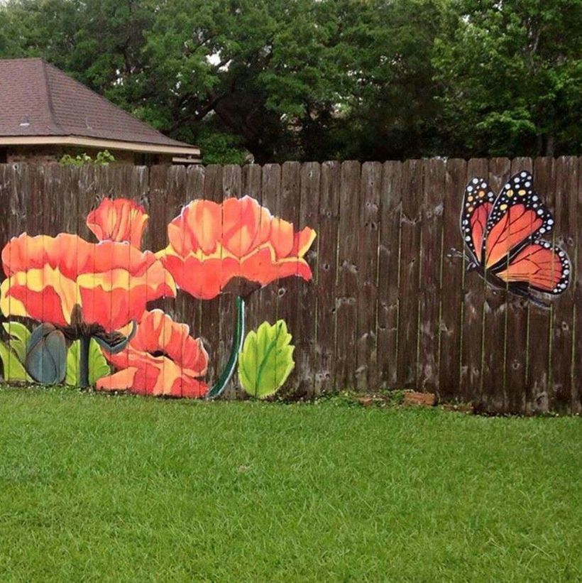 An interesting painting fence for garden with flowers and a monarch butterfly making its way over to some bright garden blossoms.