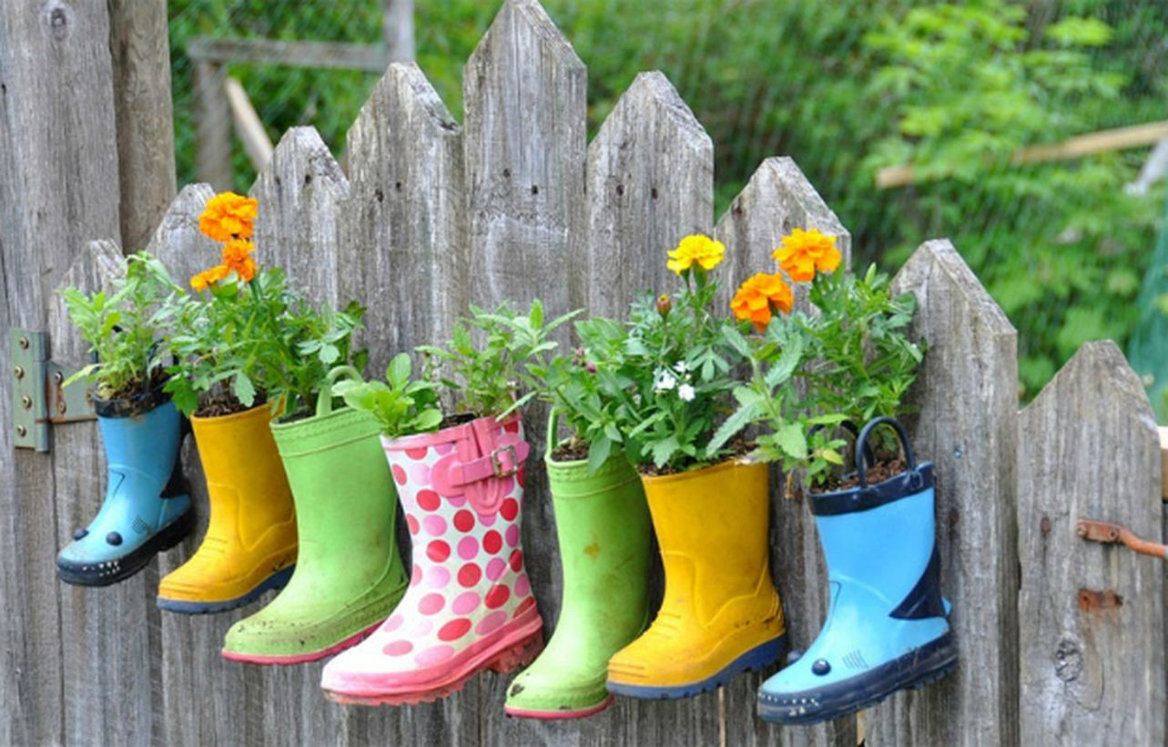 An interesting plant decoration for garden with rain boots make planters absorbed into the fence in the children's garden area stunning.