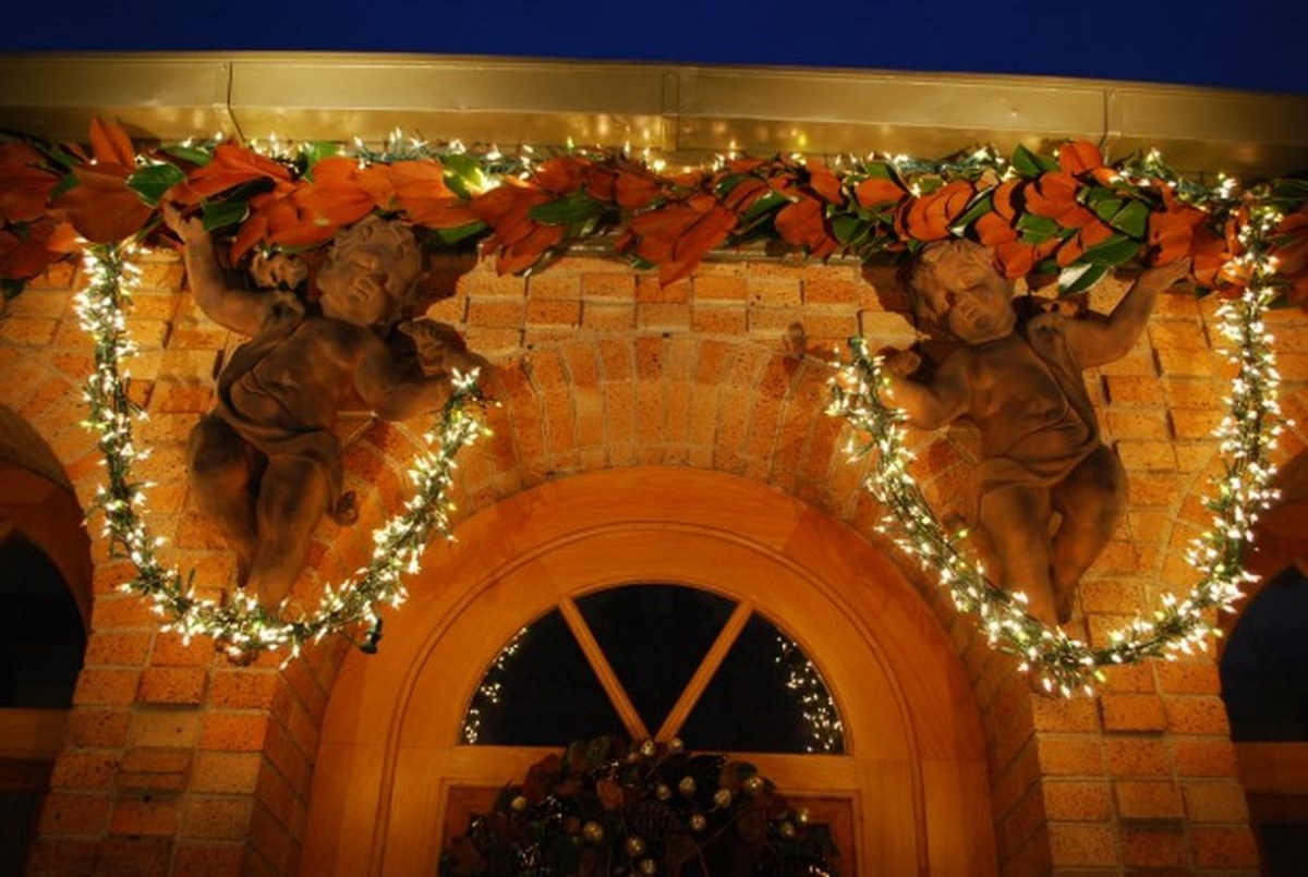Beautiful dry leaves garlands with string lamps and fairy sculptures for decoration above the door of the house