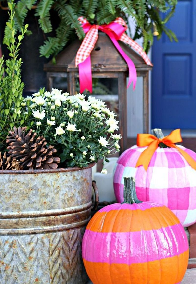 Beautiful fall outdoor decor incorporated hot pink and bright orange in her wreath, pumpkins, and lanterns