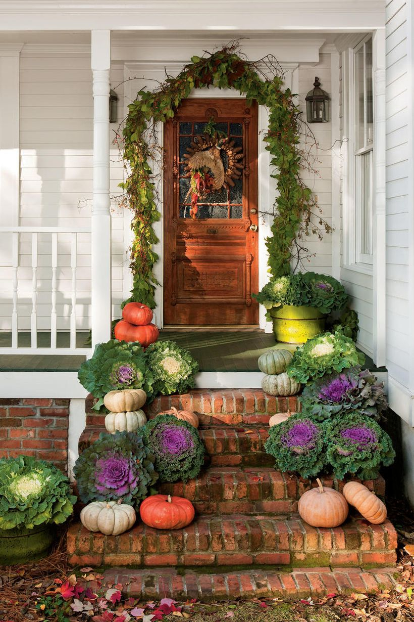 Beautiful front porch fall ideas with vines, wreath, pumpkins and green plants in pots