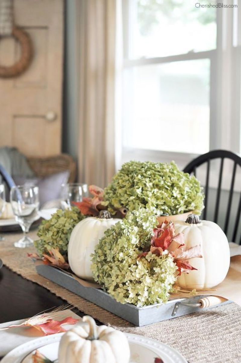 Place white pumpkins, dried hydrangeas, and fallen leaves on a tray to create a portable centerpiece in your dining room