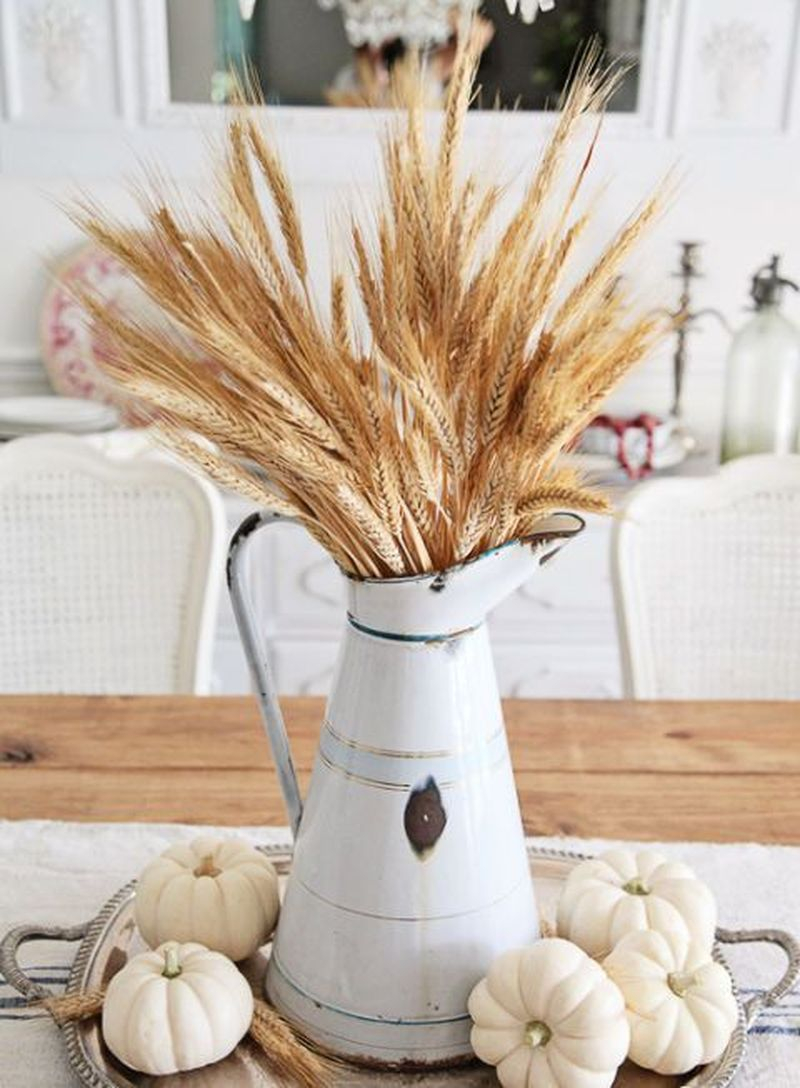 Use an antique pitcher as a vase to hold faux wheat and add neutral-colored pumpkins at the base of the pitcher to complete the look