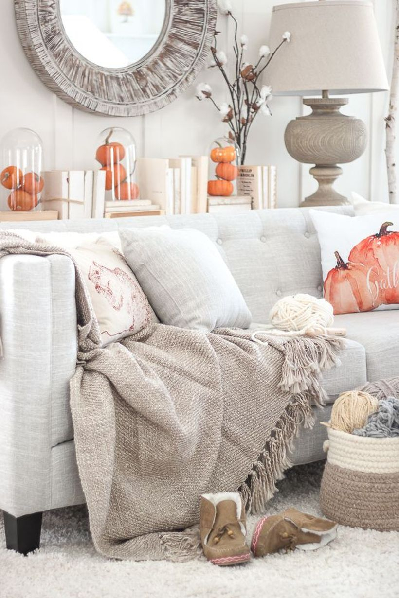 An interesting living room decoration with pumpkin decoration in jar and sofa cushions pattern pumpkin to look a cozy room