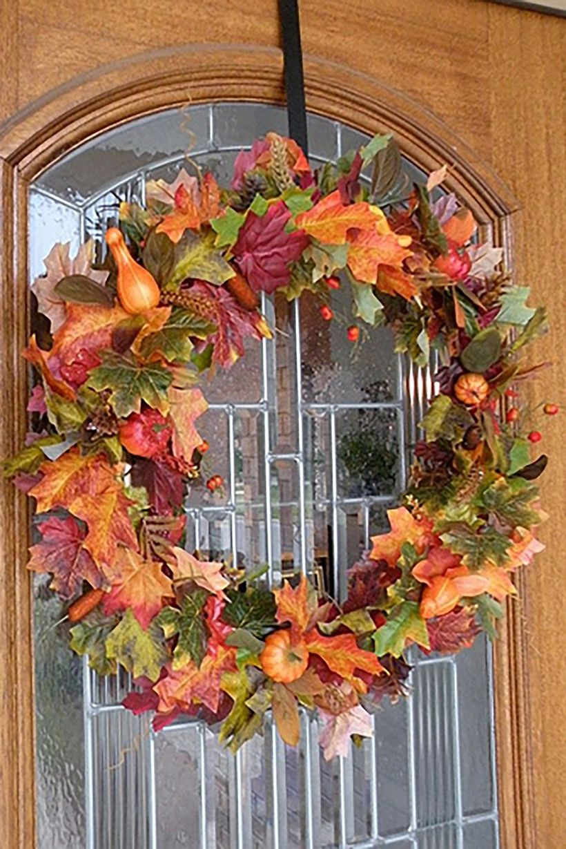 Creative dry leaves garlands with small orange pumpkins for door decoration