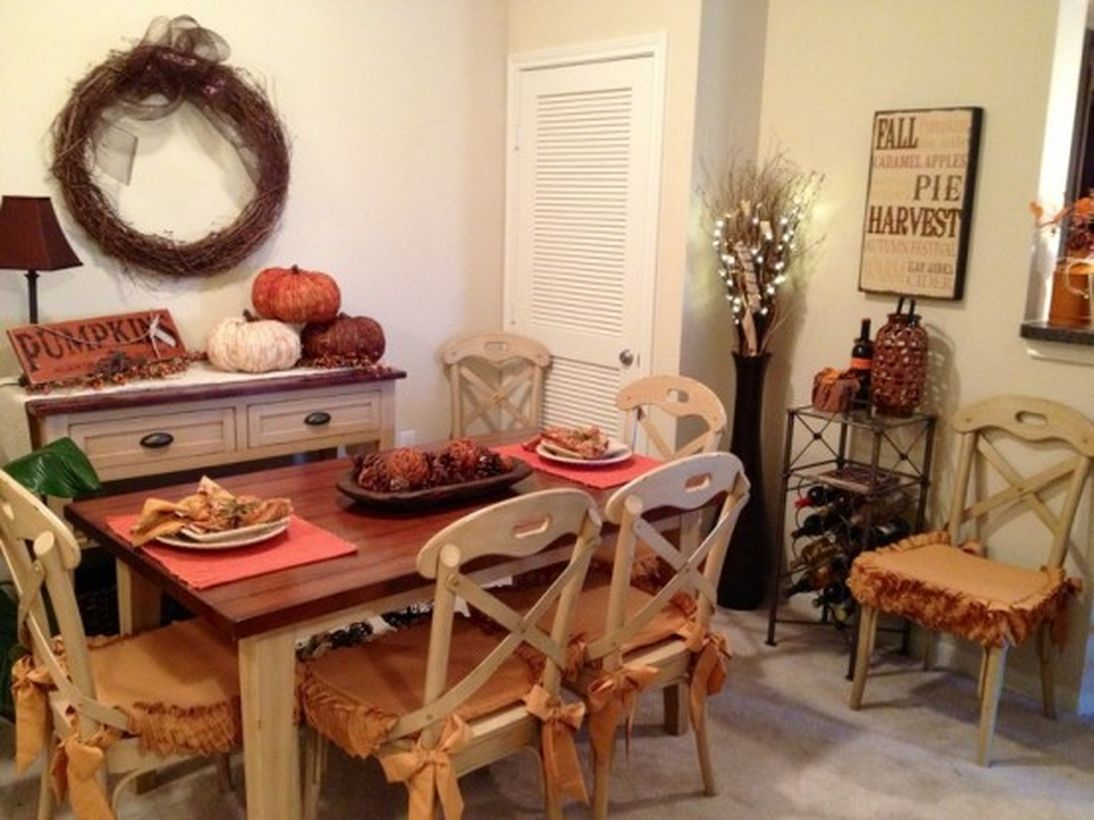 Rustic fall dining room decor ideas with pumpkin decoration on white table and wreath on the wall