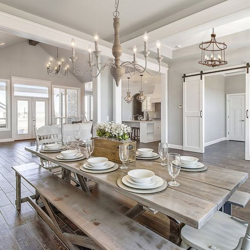 A beautiful rustic chandelier for dining room with 5-light chandelier in antique, wooden table, wooden chairs and big windows.