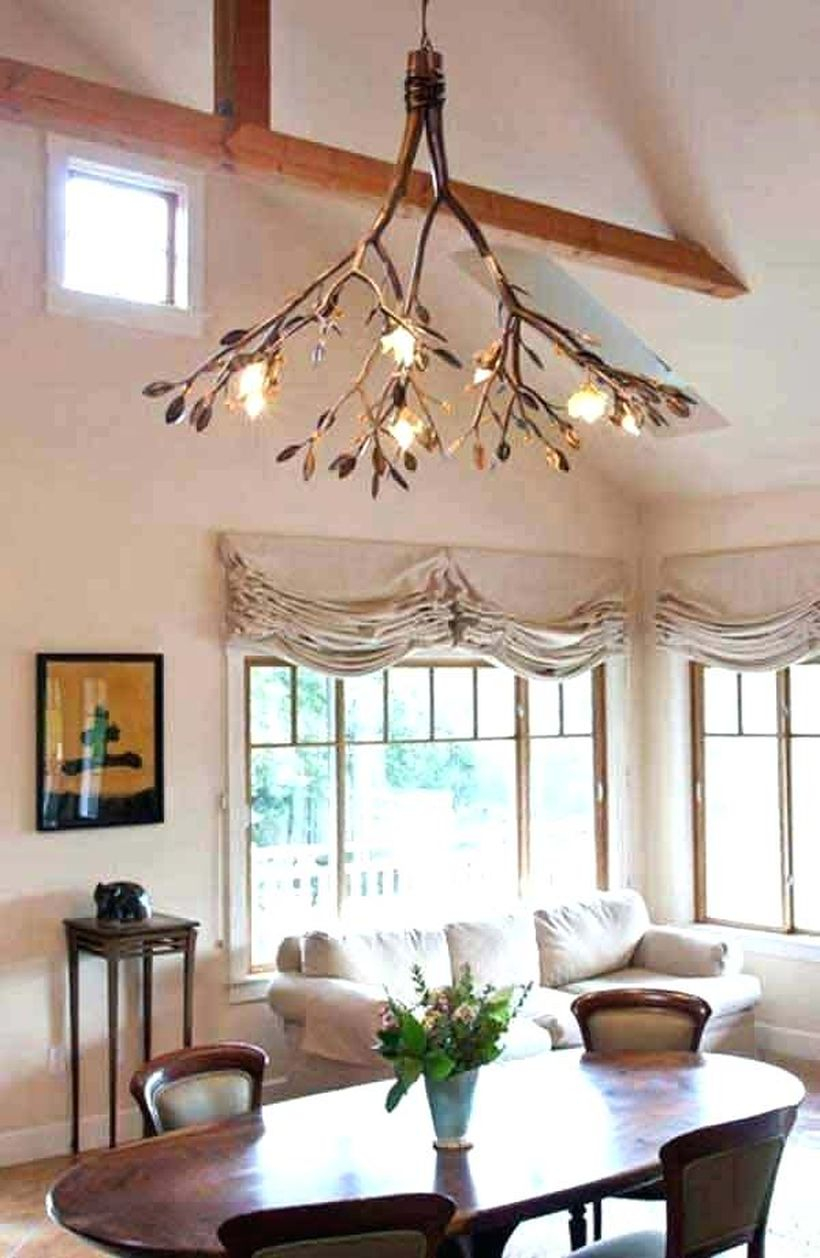 A magnificent rustic chandelier for living room with tree branch chandelier, white sofa, wooden table, wooden chairs, big window and flower vase.