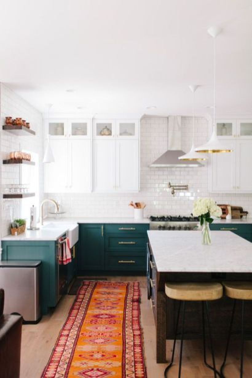 An awesome boho kitchen decor with long orange pattern carpet, green storage cabinet, white walls and island table made of wood to look good