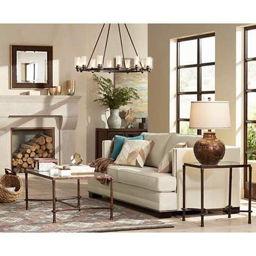 An adorable rustic chandelier for living room with wide olde bronze wagon wheel chandelier, grey sofa, iron table, small carpet and big window.