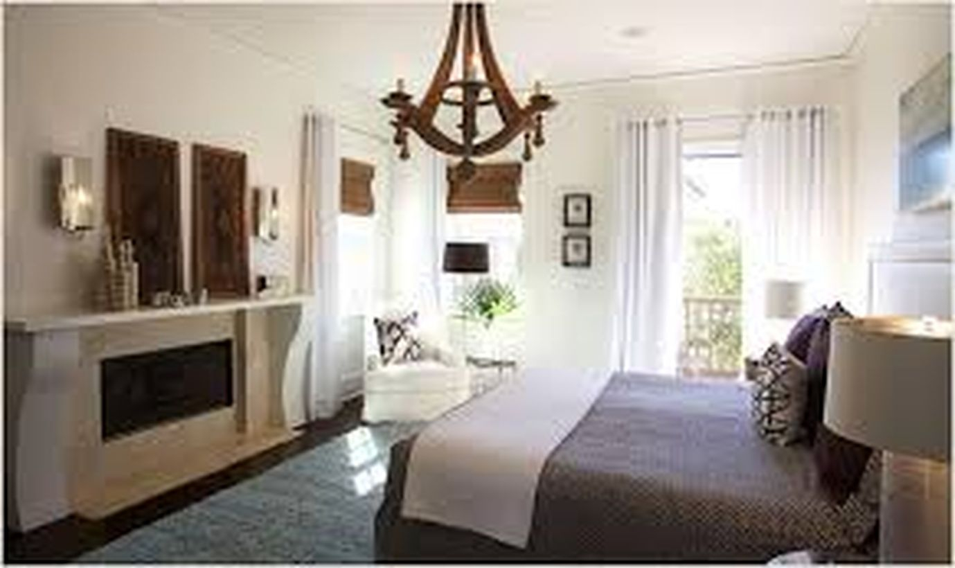 An amazing rustic chandelier for bedroom with laurel foundry chandelier, white chair on the corner, big windows, long white curtain, white blanket and decoration on the wall.