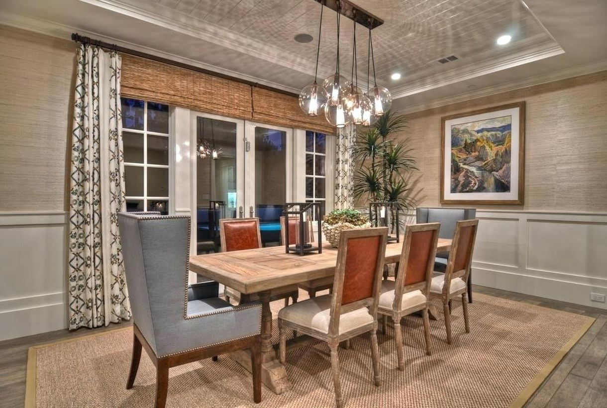 An impressive rustic chandelier for dining room with over pendant chandelier, a wooden table, wooden chairs, a large carpet and a long curtain.