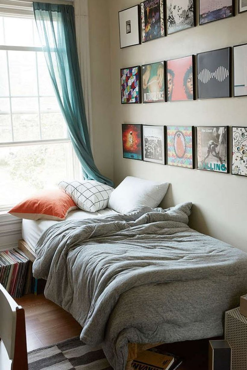 Best boys room decoration with white mattresses, gray blankets, white and orange pillows, a window, blue curtain and decorative paintings on the wall
