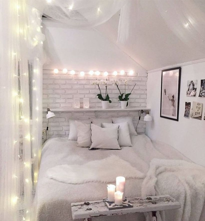 Best girls room decoration with white furry blankets, small white pillows, white walls, hanging string lamps and wooden rack on the wall