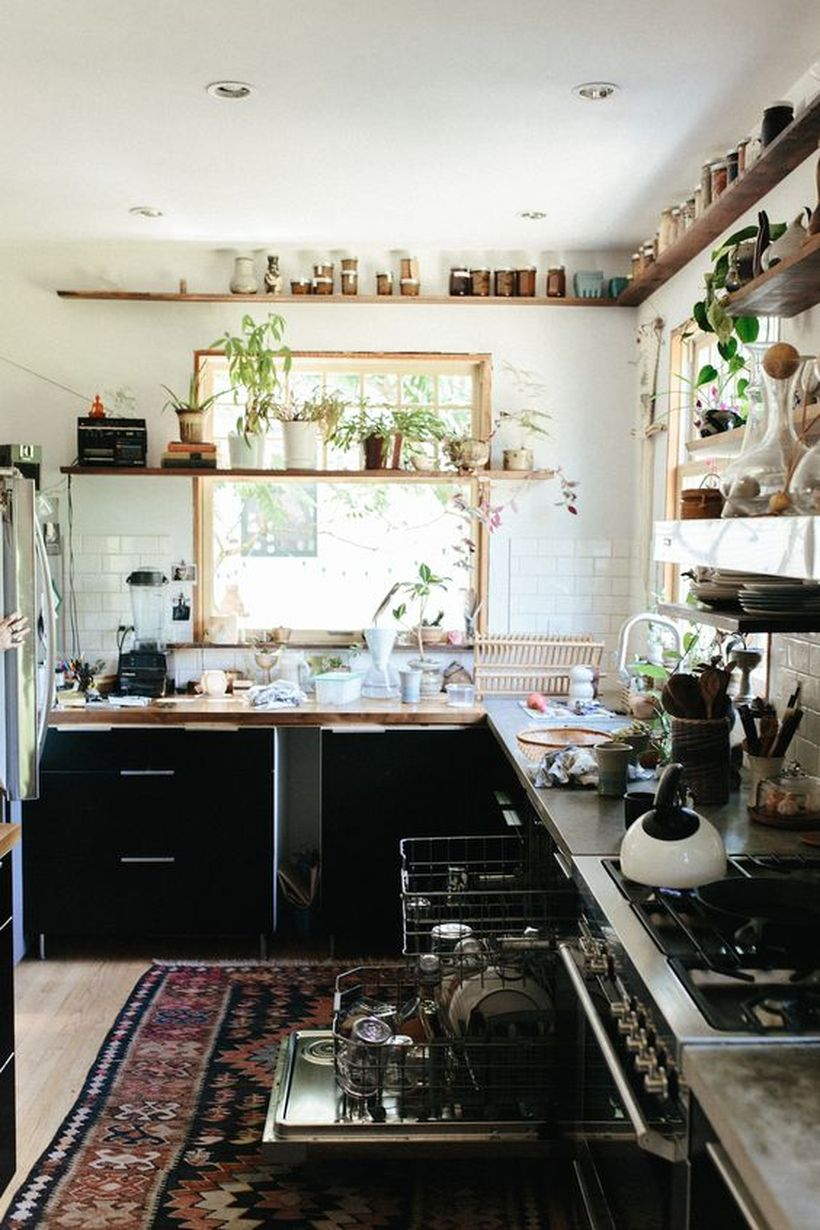 Boho kitchen decor with patterned carpets in black, storage cabinets, and wooden rack shelves to make it look cool