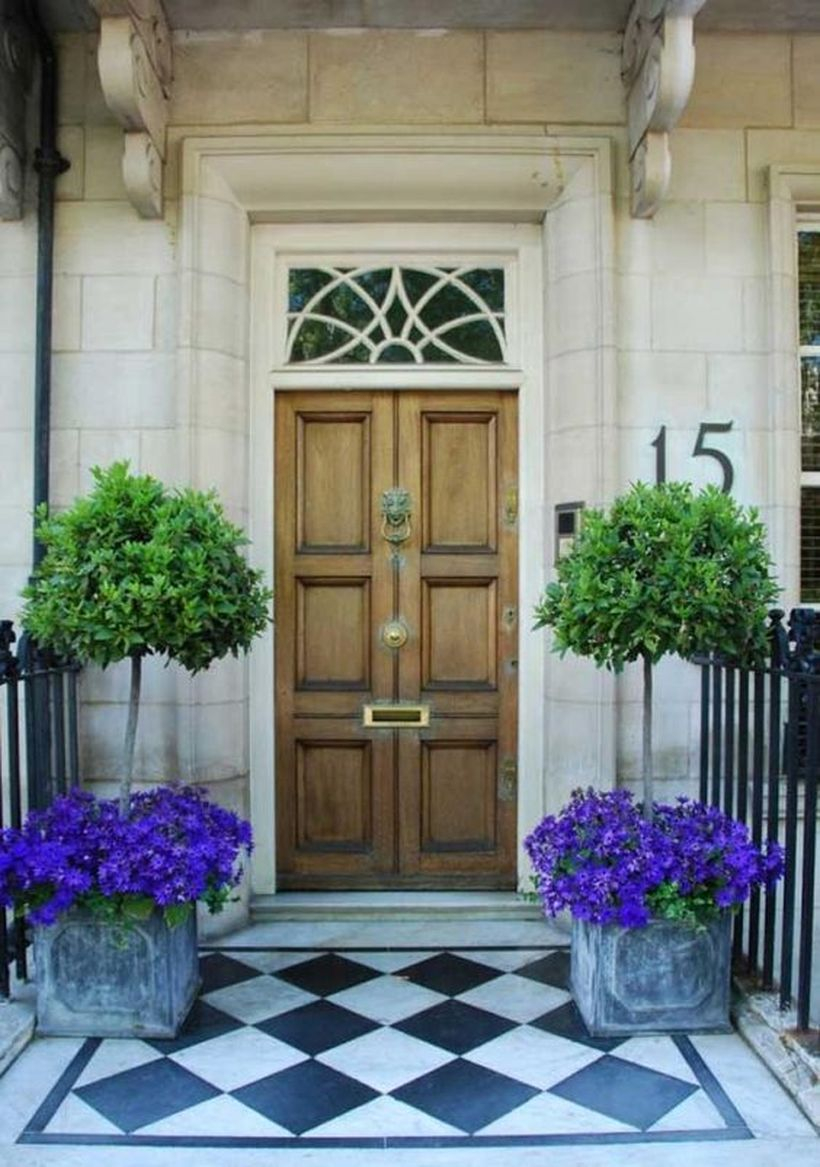 Front door decoration with purple bloom and small tree in concrete box planter